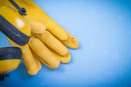 Earmuffs: Noise reduction earmuffs leather safety gloves on blue background construction concept.