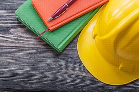 hard hat: Notepads pen safety hard hat on wooden board construction concept. Stock Photo