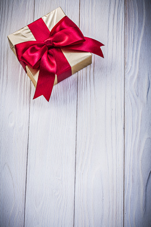 glittery: Gift box in glittery paper with bow on wooden board holidays concept.