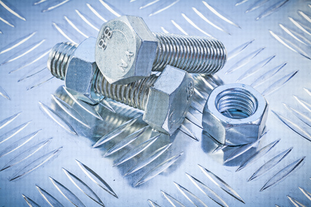 grooved: Screwbolts and construction nuts on grooved metal plate top view maintenance concept.