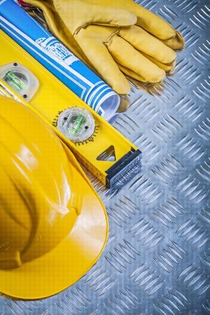 grooved: Set of blue blueprints building helmet safety gloves construction level on grooved metal plate.