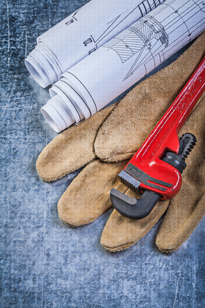 pipe wrench: Pipe wrench construction plans leather protective gloves on metallic background.