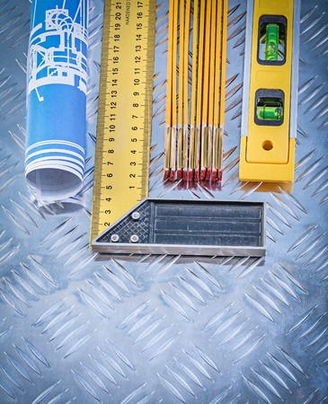 grooved: Construction plans level wooden meter try square on grooved metal plate. Stock Photo