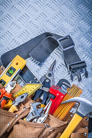 channeled: Leather tool belt with construction objects on corrugated metal pattern maintenance concept. Stock Photo