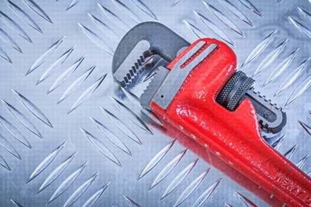fluted: Adjustable monkey wrench on fluted metal plate construction concept.