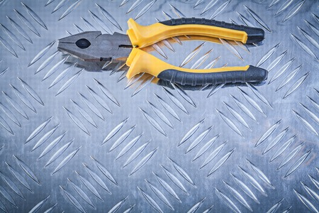 grooved: Gripping tongs on grooved metal plate construction concept.
