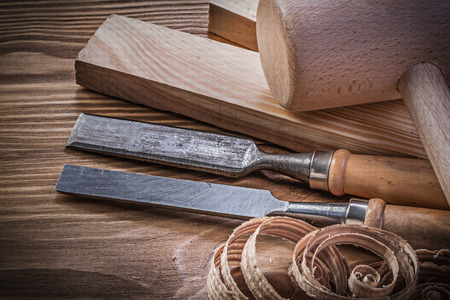 stud: Lump hammer wooden stud firmer chisels planning chips on vintage wood board. Stock Photo