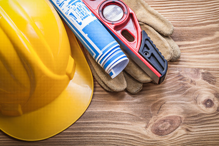 construction level: Hard hat safety gloves construction level blue blueprint on wooden board.