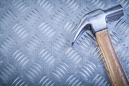 channeled: Claw hammer with wooden handle on corrugated metal plate construction concept.
