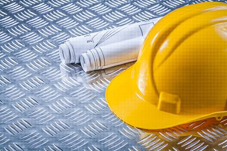 grooved: Blueprint rolls building helmet on grooved metal plate construction concept.
