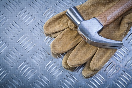 grooved: Claw hammer safety gloves on grooved metal plate construction concept.