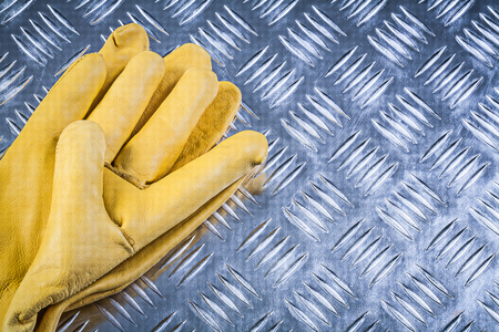 fluted: Pair of leather safety gloves on fluted metal sheet construction concept. Stock Photo