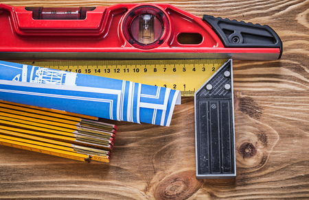 square ruler: Construction level blue blueprint wooden meter square ruler on vintage wood board. Stock Photo