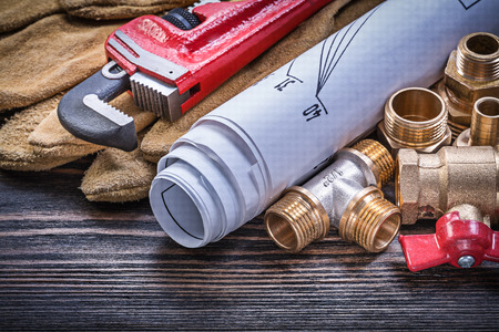 protective gloves: Protective gloves monkey wrench blueprints brass plumbing fittings gate valve on wooden board. Stock Photo
