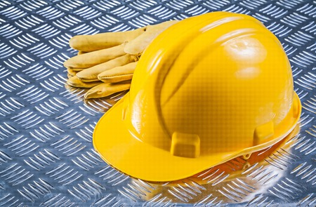 fluted: Safety leather gloves hard hat on fluted metal plate construction concept.