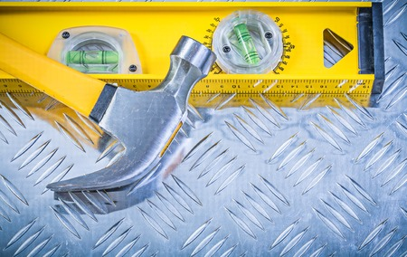 Claw hammer construction level on corrugated metal sheet. Stock Photo