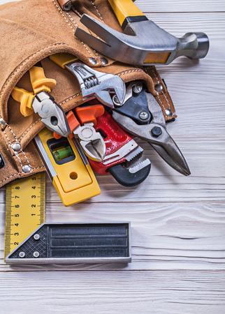 alicates: cinturón de herramientas de cuero marrón con herramientas de construcción a bordo de madera directamente encima.