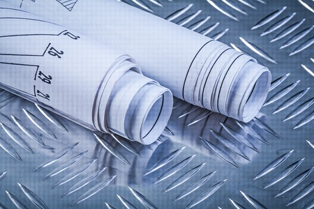 fluted: Rolled construction drawings on fluted metal background front view.