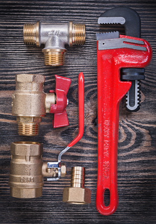 pipe wrench: Composition of pipe wrench brass fittings water valve on wood board plumbing concept.