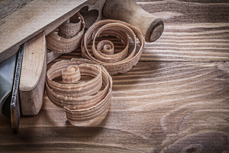 scobs: Shaving plane planning chips on vintage wooden board construction concept.