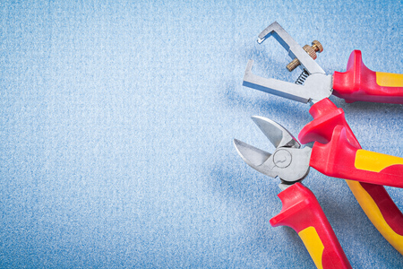 stripper: Wire stripper pliers nippers on blue background electricity concept.