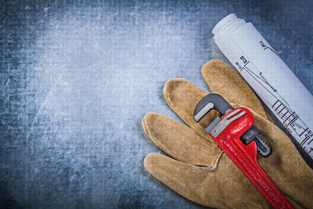 stainless steel range: Monkey wrench protective gloves blueprints on scratched metallic background plumbing concept.