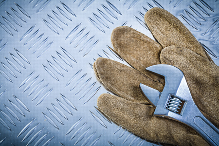 grooved: Safety gloves adjustable wrench on grooved metal plate construction concept. Stock Photo