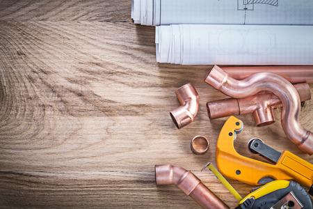 wood cutter: Construction drawings measuring tape water pipe cutter connectors on wood board plumbing concept. Stock Photo