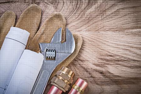 niples: Guantes de seguridad de cobre planos de tuber�as de agua de la manguera pezones llave inglesa ajustable en el concepto de tablero de madera de fontaner�a.