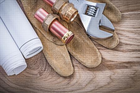 pezones: Guantes protectores planos de cobre de tuberías de agua manguera pezones llave ajustable en concepto de tablero de madera de fontanería.