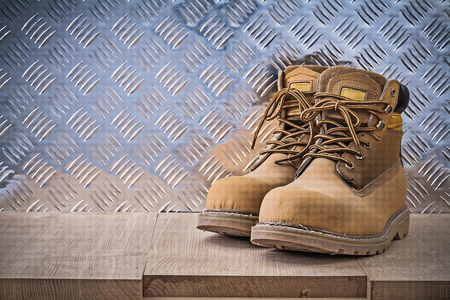 safety boots: Pair of safety lace boots wooden board fluted metal sheet construction concept.