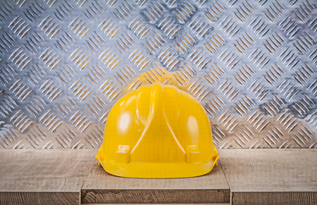 channeled: Safety hard hat wooden board channeled metal sheet construction concept.