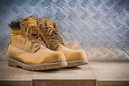 grooved: Pair of protective waterproof boots wooden board grooved metal sheet construction concept.