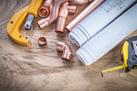 stainless steel range: Construction drawings measuring tape copper water pipe cutter fittings on wooden board plumbing concept. Stock Photo