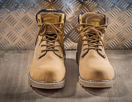 zapatos de seguridad: zapatos de cordones de seguridad a prueba de agua tabla de madera concepto de la construcción placa de metal corrugado. Foto de archivo