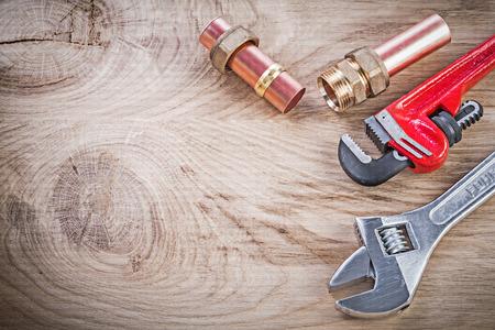 pezones: tubería de agua de cobre boquilla para manguera con rosca mono llave inglesa ajustable en el concepto de tablero de madera de fontanería. Foto de archivo