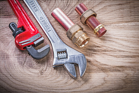 pipe wrench: Copper water pipe wrench nipple hose connectors adjustable key on wooden board plumbing concept. Stock Photo
