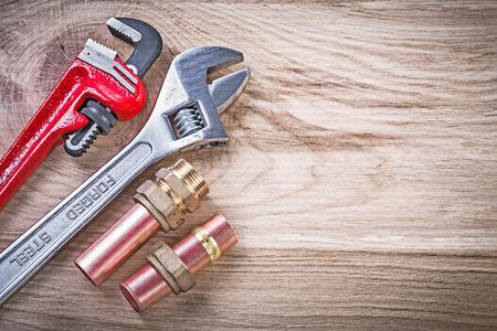 pezones: Conjunto de tubería de agua de cobre conectores de manguera llave inglesa ajustable en el concepto de tablero de madera de fontanería.