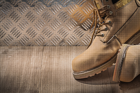 safety boots: Safety waterproof lace boots wooden board channeled metal plate construction concept.