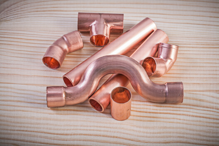 stainless steel range: Copper pipe fittings on wooden board plumbing concept. Stock Photo