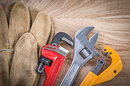 Composition of safety gloves adjustable spanner monkey wrench pipe cutter on wooden board plumbing concept. Stock Photo