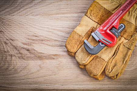 pipe wrench: Safety gloves pipe wrench on wooden board plumbing concept. Stock Photo