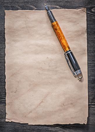 pluma de escribir antigua: Vintage paper sheet fountain pen on wooden board top view. Foto de archivo
