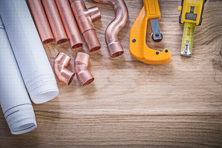 Construction plans tape line water pipe cutter fittings on wood board plumbing concept.