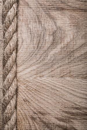 wood backgrounds: Vintage jute rope on wooden board.