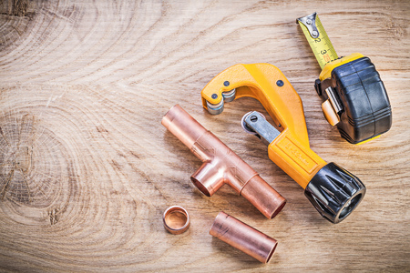wood cutter: Copper water pipe cutter fittings tape measure on wood board top view plumbing brassware concept. Stock Photo