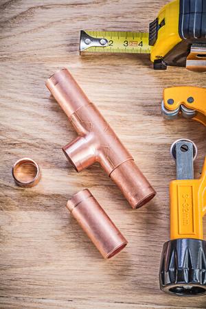 fixtures: Copper water pipe cutter fixtures tape measure on wooden board vertical view plumbing brassware concept.