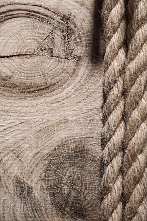 backcloth: Vintage spirally twisted flax ropes on wooden board top view.
