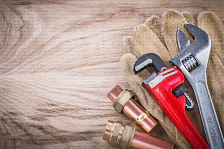 pezones: Guantes de seguridad de tubería de agua de cobre de manguera llave de llave inglesa ajustable pezones en el concepto de tablero de madera de fontanería. Foto de archivo