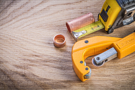wood cutter: Assortment of brass water pipe cutter measuring tape on wood board plumbing concept.